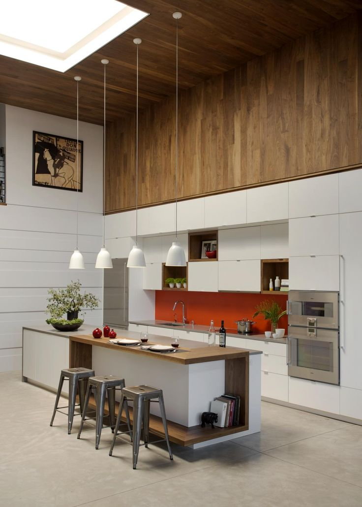This kitchen was renovated with custom white cabinetry and designed to include more storage, larger prep surfaces and energy efficient appliances. Walnut wood panels wrap the wall and ceiling, showing off a skylight and four pendant lights positioned over the kitchen island. A bright orange backsplash adds a pop of color.