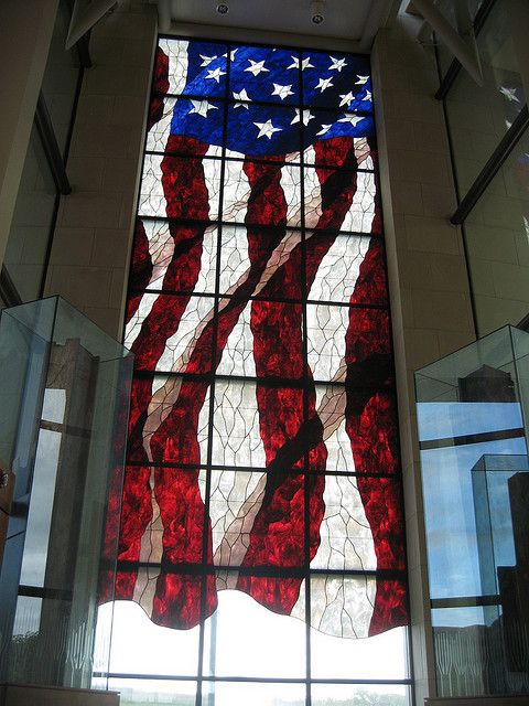 This stained glass U.S.  flag is located at the The Robert J. Dole Institute of Politics  at the University of Kansas to memorialize the Americans killed in the Sept. 11, 2001, terrorist attacks.  Each piece of which was designed, fired and assembled in America. Two beams from One World Trade Center  flank the flag and stand as they were when recovered. It is thought to be the largest stained glass American flag in the world.