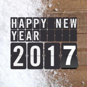 Stoere nieuwjaarskaart met houten achtergrond met sneeuw en in zwarte klaptekst Happy New Year en met klapcijfers 2017.