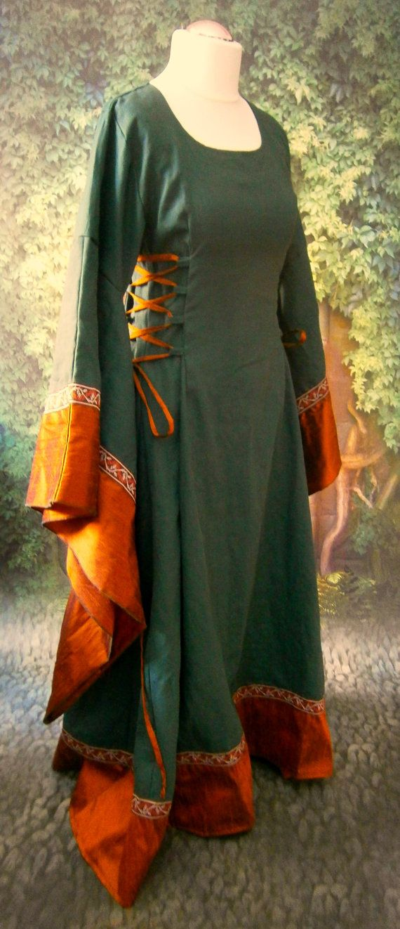 This is a simple but elegant dress. Perfect for the medieval market, reenactment, or for LARP. This dress is made out of soft linen in forest green and beautiful silk in rust orange. Decorated with meters of beautiful trim with tendrils in rust and maroon at the sleeves and the bottom part of the dress. It has a corset type lacing at the sides in contrasting rust silk for a nice adjustable fit and long bell shaped sleeves. This dress will be available in many colors, please ask for your…