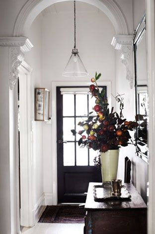 Bright white hallway with dark grey front door - similar to Farrow and Ball Railings or Off Black