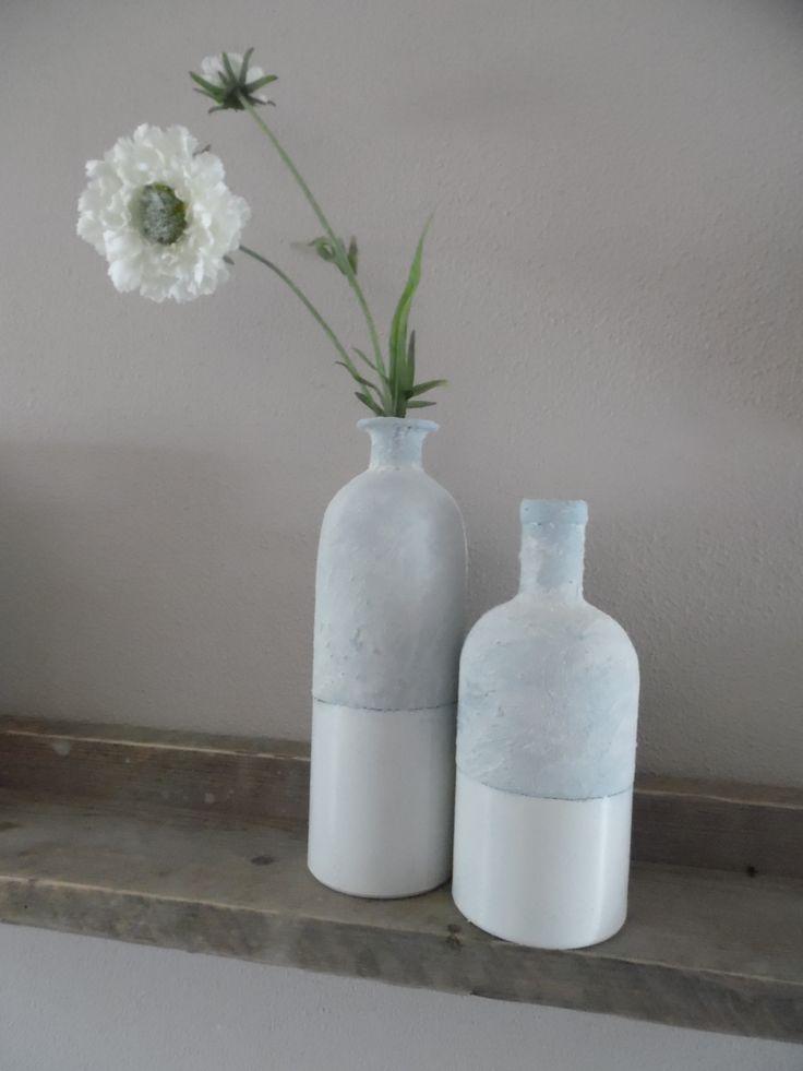 Close up glazen flessen behandeld met muurvuller en daaroverheen bloem..