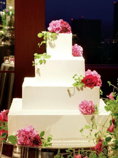 シンプルなスクエアケーキにピンクのミニブーケが鮮やかなアクセント。