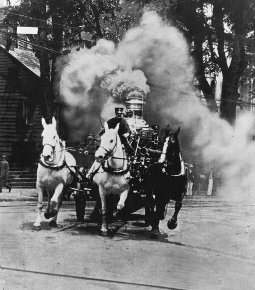 A horse drawn fire-engine with a steam operated water pump rushes to the fire, somewhere in the US, circa 1910