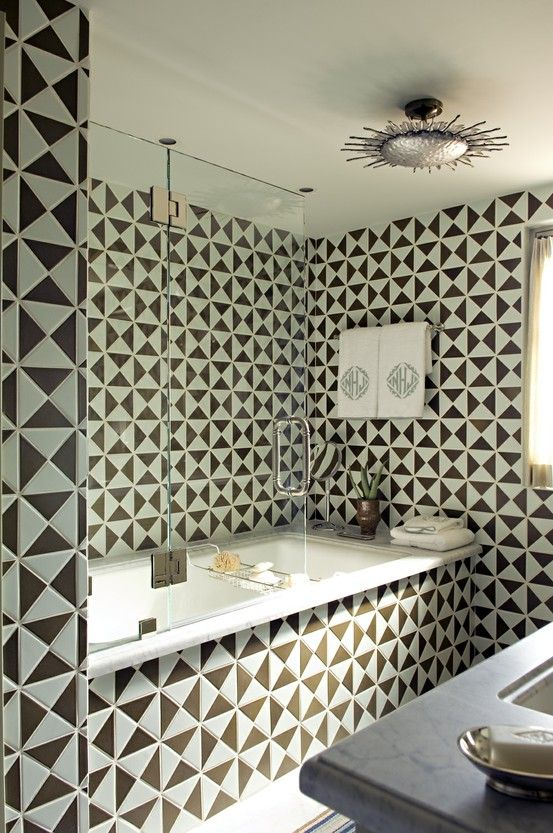 Triangle shaped tile created this great geometric bathroom! by designer  Cathy Kincaid. Really cool, but Holy Cow am I glad I didn't have to tile it!