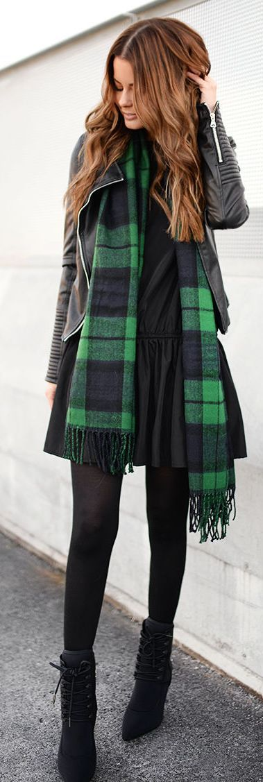 black leather jacket, wide black and green plaid scarf draped around neck, black dress, opaque black hose, and black combat boots or heeled ankle lace up booties.
