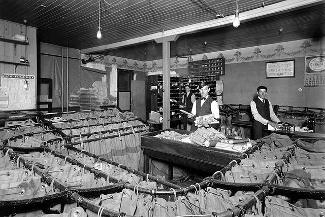 Employees sort mail into sacks at the Lethbridge Post Office, April 1912. #Edwardian #professions #vintage #Canada