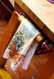 Vintage rolling pin used as a towel bar.