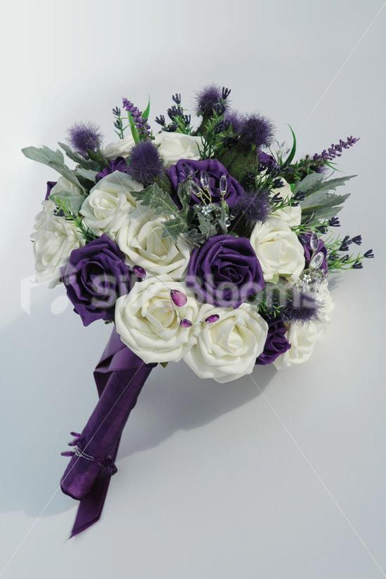 I'm kinda liking the darker purple. This is an arrangement of ivory roses, thistles, sea holly and heather, with blue tartan ribbon entwined throughout it.