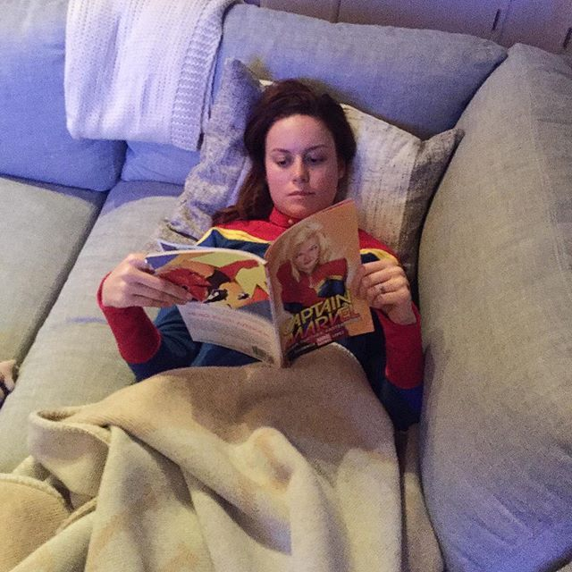 Captain Marvel herself, Brie Larson dressed in Captain Marvel pj's reading a Captain Marvel comic.
