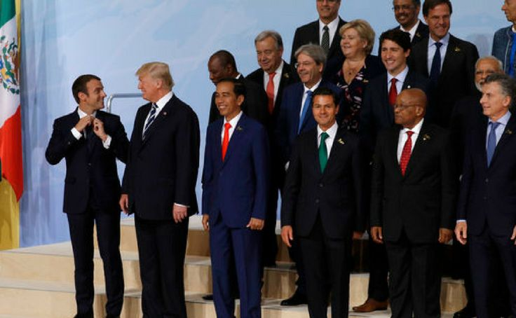 France's president Emmanuel Macron, left, adjusts his tie as he jokes with, from left, US president Donald Trump, Indonesian President Joko Widodo, Senegal's President Macky Sall and Mexican President Enrique Pena Nieto during the family photo. Reuters