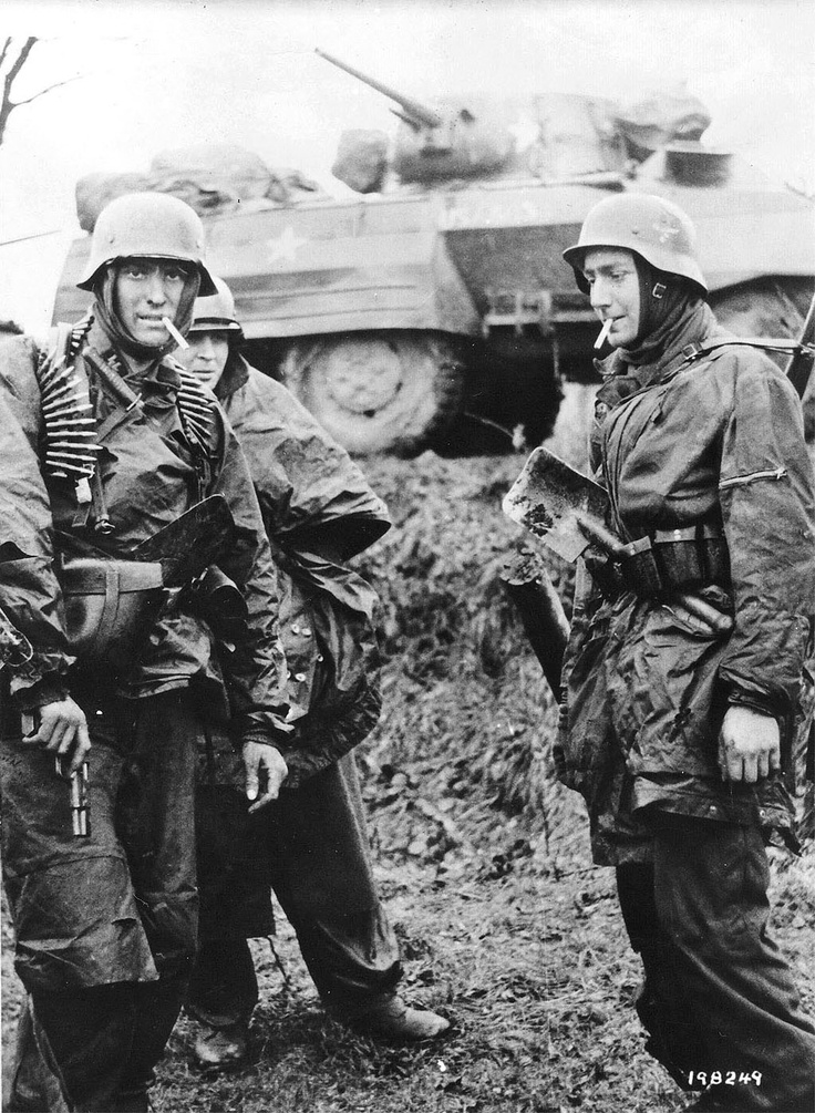 This is the complete frame of one of the most famous stills from the German side in World War II. It is one of several taken (along with newsreel film) on December 18, 1944 near Poteau, Belgium during the Battle of the Bulge. The men are smoking captured American cigarettes, and they are part of the 1st SS Panzer Division, Kampfgruppe Hansen. The man on the left is holding an FN High Power pistol, and is draped in a 7.92mm MG42 ammunition belt.