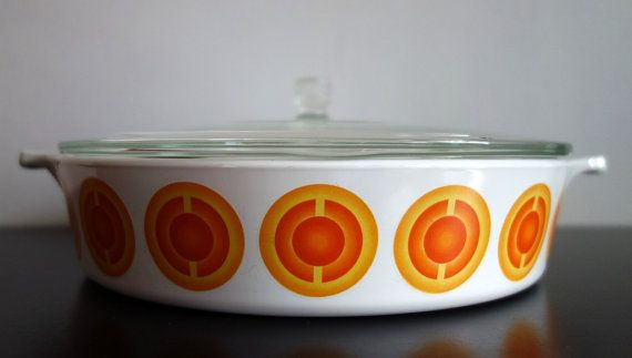 This lidded oven/casserole dish was produced in Holland in the 1970s and is 18cm. According to the Pyrex Pyroflam website, it is made from a material originally developed in partnership with the American Space Agency for the outside of space shuttles. Pyroflam products are suitable for all sorts of ovens and cooker tops, apart from induction, and due to their strength are suitable for long lasting high temperatures.  This particular dish is in excellent condition and shows very few signs...