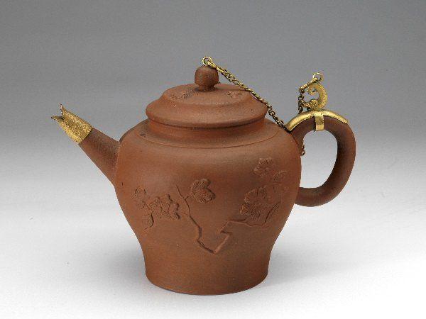 Theepot, rood steengoed, reliëfbloemtak, ketting verguld koper - Milde, Ary de - Museum ArnhemMilde, Ary de (1634 – 1708) Collectie:Toegepaste kunst Materiaal:steengoed, koper Categorie:Eet-, drink- en keukengerei Afmetingen: hoogte:11.8 cm breedte:18.0 cm diameter:10.0 cm