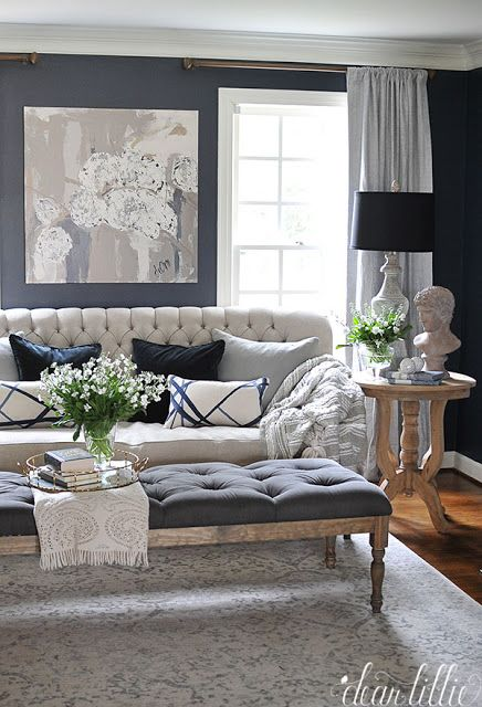 Dark Blue Walls Add Dimension To An Off White Sofa, Misty Gray Curtains,  And A Pale Patterned Rug.