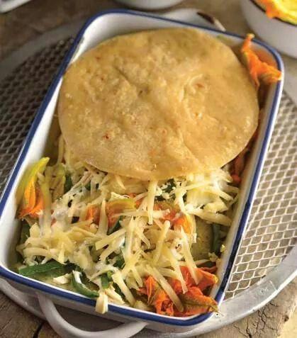 """""""Pastel azteca"""" Ingredientes: ·12 tortillas de maíz fritas ·1 kg de tomate verde ·1 cebolla ·1 manojo grande de cilantro ·3 dientes de ajo ·4 chiles de árbol secos ·1 taza de rajas de chile poblano ·2 tazas de flor de calabaza ·2 tazas de pechuga de pollo deshebrada ·1 1/2 tazas de crema ·2 tazas de queso manchego rallado.Preparación: 1. Precalienta el horno a 180oC. 2. Hierve los tomates junto con la cebolla, el chile de árbol, el cilantro y el ajo. Cuando el tomate esté cocido, muele la…"""