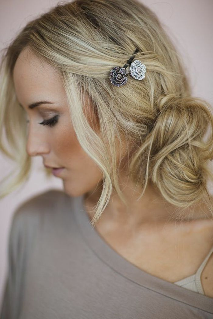 coiffure de femme avec chignon messy de coté raie au milieu et deux accessoires cheveux en forme de roses