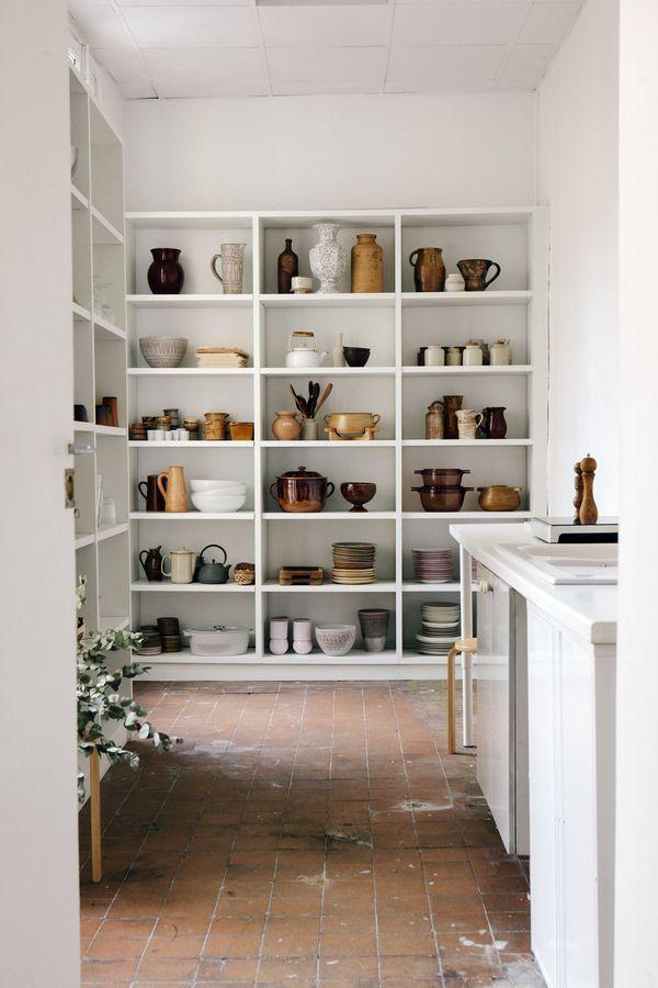 White bookshelves storing kitchen bowls and vessels