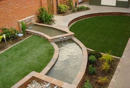 A round and a semi-circular lawn separated by a raised rill.