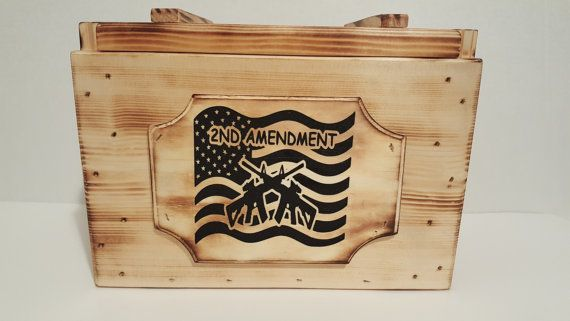 Handcrafted Wooden ammo box,,made to look like the old military style ammo boxes. Has wood handles, and has an wood etched 2nd amendment plaque on the front, flag decal on removal top. Size 11.5 x 8.5 x 7.25.  Keep several boxes of your favorite ammo in this old looking military style wood ammo box, or use it to keep all your favorite keepsakes in. Makes a great gift for that hard to buy for person.  All wood ammo boxes are ready for shipping. Also adds a great center piece to that hunting…