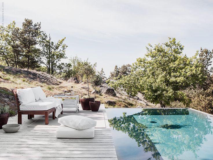 Inred en krispigt vit lounge med snacks och en trave fräscha handdukar inom räckhåll för en lyxig hotellkänsla vid poolen.