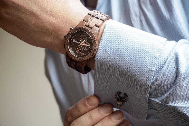 Man in blue shirt wearing wooden JORD Conway watch adjusts stag cufflinks