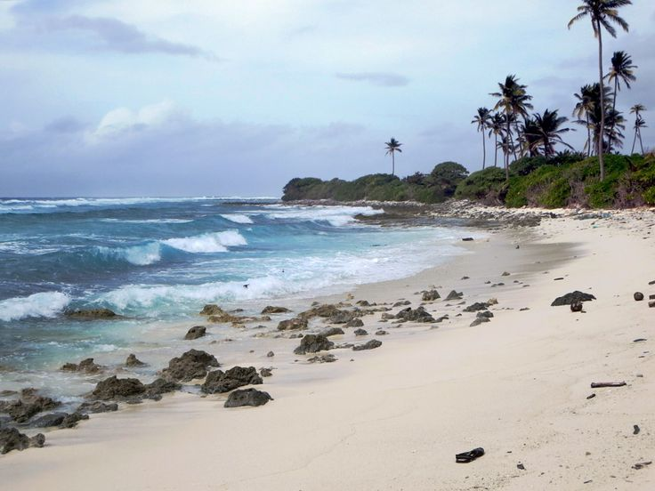 Ocean waves crash into a beach on the east side of Home Island, Cocos (Keeling) Islands.