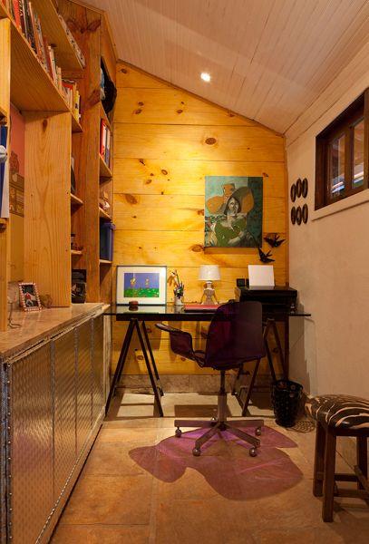 As paredes revestidas em madeira e as portas metalizadas estão em harmonia neste home office. Destaque para cadeira roxa em acrílico. Projeto do escritório MMMundim Arquitetura e Interiores.