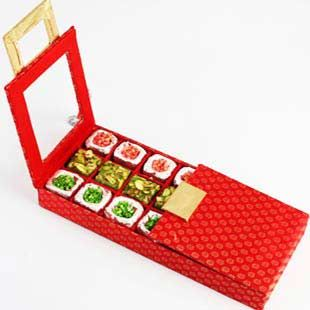 A beautiful red wooden stain box containing Assorted Cashew and Pistachio delicacies. Net weight:550 gms.http://www.exoticabazaar.com/view/9108-68-ghasitaram-s-red-buckle-mithai-box.html