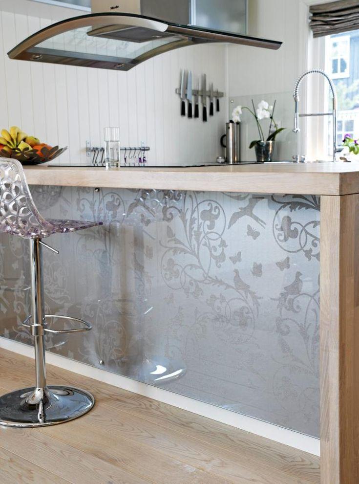 Kjøkkenøya av tre er dekorert med tapet og glass, og over henger en majestetisk og buet kjøkkenvifte.