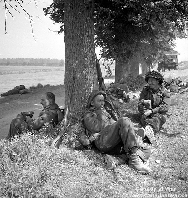 Canadians capture Caen - The Highland Light Infantry of Canada take a quick rest on the bank of the Orne River. 18 July 1944, Caen, France (vicinity).