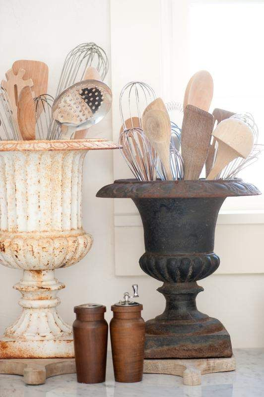 Use rusty urns to hold kitchen utensils