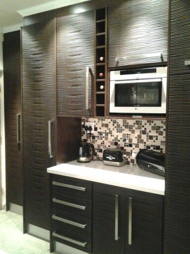 African wenge kitchen, with African style door panels. www.obsidointeriors.co.za