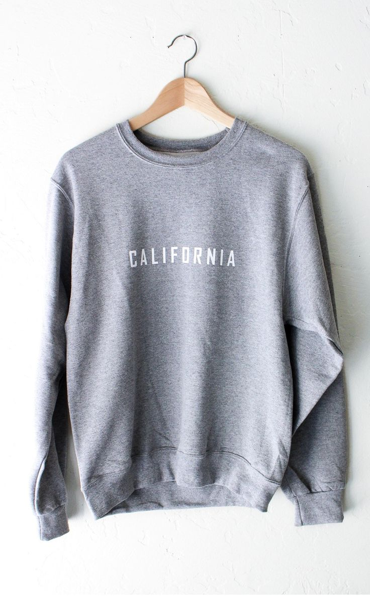 """- Description Details: Chill in our soft & cozy oversized sweater in grey with print featuring 'California'. Brand: NYCT Clothing. Unisex, oversized/loose fit. Measurements: (Size Guide) XS/S: 40"""" bus"""