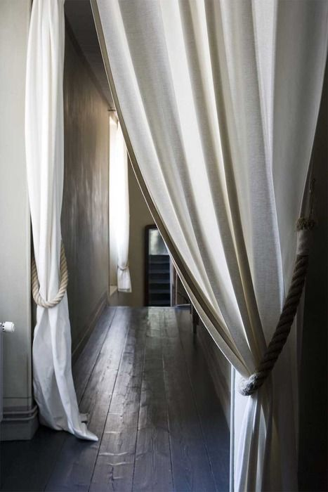 Medium weight canvas or (cotton /blend] curtains held back with thick braided rope. Divide space, create privacy, adjust lighting all in one.