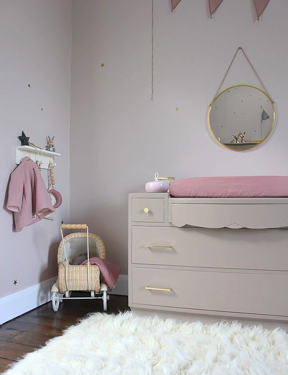 Une belle commode beige taupe avec des poignées dorées dans une chambre bébé