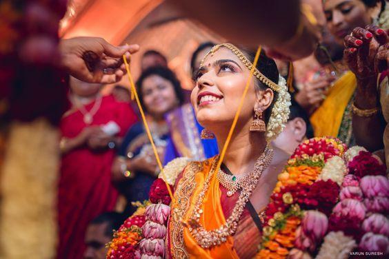 South Indian bride. Temple jewelry. Jhumkis.Orange silk kanchipuram sari.Braid with fresh jasmine flowers. Tamil bride. Telugu bride. Kannada bride. Hindu bride. Malayalee bride.Kerala bride.South Indian wedding: