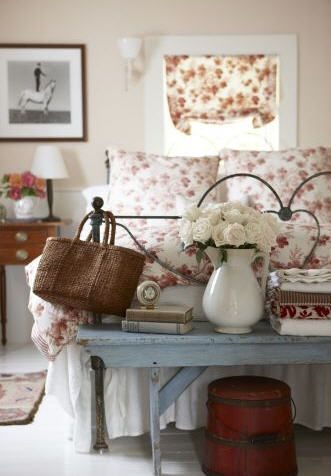 Pretty combination of pink and white flowers, rustic paintwork , a worn wicker basket and a couple of well read books
