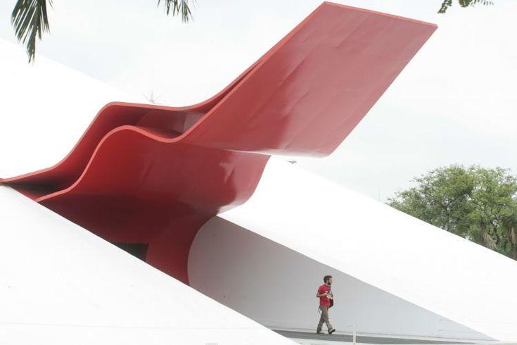 """Projetado por Oscar Niemeyer nos anos 1950, mas erguido apenas em 2004, o Auditório do Parque do Ibirapuera tem 4.870 m² de área construída e é uma das mais importantes casas de espetáculos de São Paulo, com capacidade para 800 pessoas. A construção, além disso, abriga três grandes obras de arte: logo na entrada principal está instalada a escultura de Oscar Niemeyer batizada como """"Labareda"""" (na foto), que faz as vezes de marquise do edifício. Já no hall principal há uma escultura assinada…"""