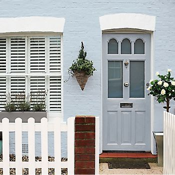 Baby blue masonry paint with a blue front door and a standard rose bush