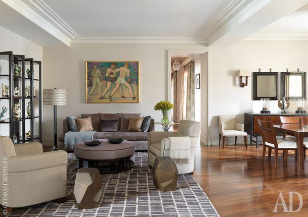 """Гостиная. Картина 1930-х годов """"Боксеры"""" куплена в Нью-Йорке. Диван, ковер и пуф сделаны на заказ. В зоне столовой слева — бра, J. Robert Scott, сделанный на заказ комод и пара зеркал, Baker, как и придиванный столик."""