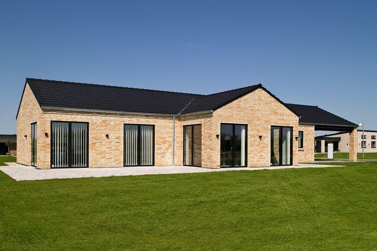 Huset med murede gavle og gesims, opført i gul/rosé blødstrøgne mursten, sorte betontagsten og matchende sorte 3 lags træ/aluvinduer.