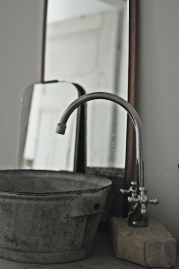 zinken teil met beton onder kraan. Simpel en praktisch. Kijk voor oude brocante zinken teilen, emmers en gieters bij www.old-basics.nl