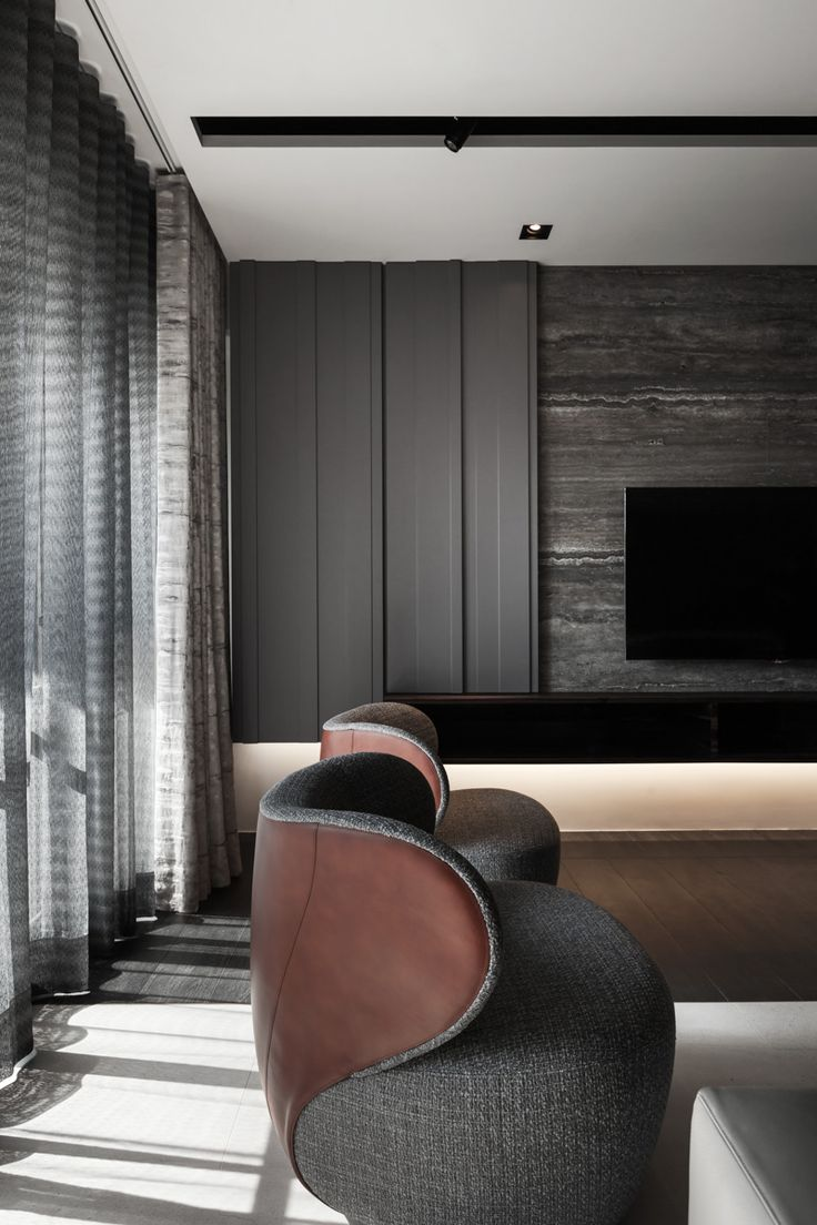 very male and elegant. combination of grey stone, grey wall panels, dark wood and linen like upholstery