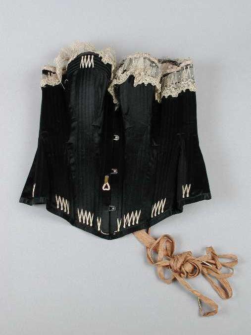 Korset van zwart satijn, sterk gebaleineerd. De uiteinden van de baleinen zijn onder en boven met roze borduurzijde verstevigd. Bovenrand afgebiesd met een strook crèmekleurig kant en een roze lintje. De boezem wordt benadrukt door horizontaal geplaatste baleintjes. Binnenzijde bekleed met roze satijn. Aan de voorzijde een busksluiting, aan de achterzijde een rijgvetersluiting met roze zijden lint. datering1890 - 1895