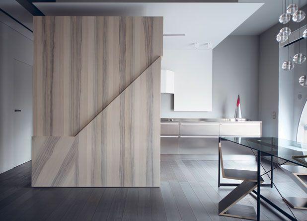 La cucina a vista con l'imponente mobile in legno fraké su disegno di Marcante e Testa, realizzazione Materia Design, il tavolo Asnago & Vender di Pallucco con le storiche sedie Zig-Zag di Gerrit Rietveld, prodotte da Cassina, e il lampadario 14.14 di Bocci.