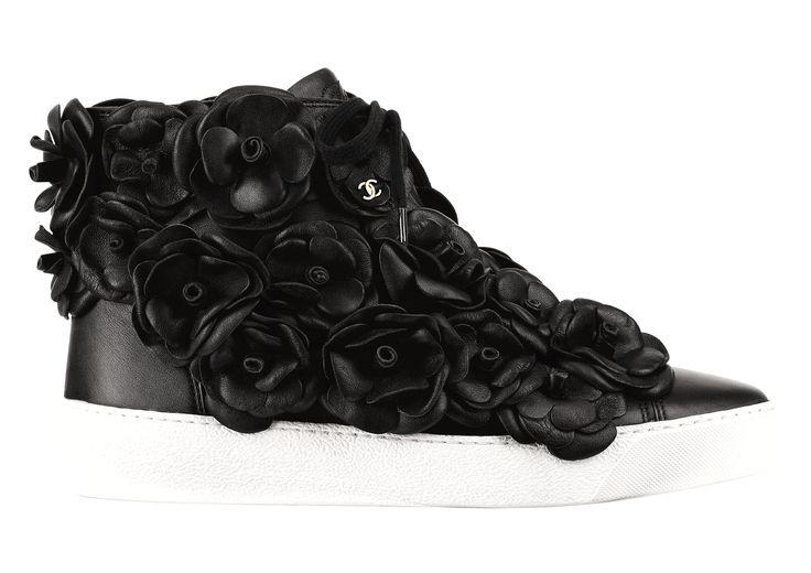 Les sneakers en cuir Chanel décorées du camélia emblématique de la maison. En version rose poudré ou noire, elles relèvent le défi d'allier raffinement et style casual. Issues de la pré-collection printemps-été 2013/2014, elles n'ont pas cessé de faire parler d'elles depuis leur lancement… Tout le monde leur court après ! Un comble pour des baskets ? © CHANEL
