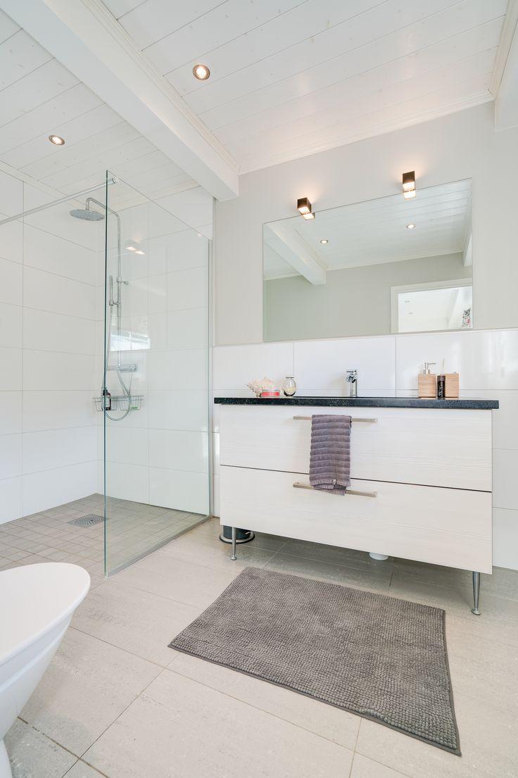 Mycket fräscht duschrum, helkaklat, glas och blanka ytor och med träpanel i tak Slingervägen