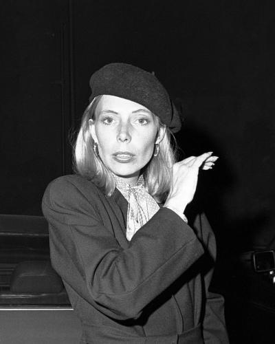 Joni Mitchell- looking glammed up in make up and a beret.
