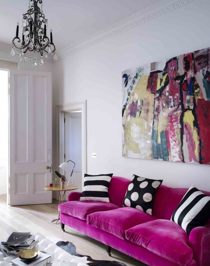 White Living Room With Pink Velvet Sofa And Chandelier